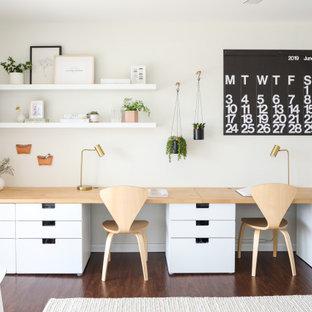 На фото: маленький кабинет в современном стиле с белыми стенами, темным паркетным полом и коричневым полом без камина