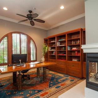 Modelo de despacho mediterráneo, grande, con paredes grises, suelo de baldosas de cerámica, chimenea de esquina, escritorio independiente y suelo beige
