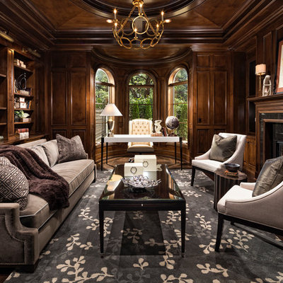 Example of a tuscan freestanding desk dark wood floor home office design in Los Angeles with a standard fireplace