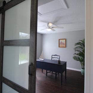 他の地域の広いビーチスタイルのおしゃれな書斎 (グレーの壁、ラミネートの床、暖炉なし、自立型机、茶色い床) の写真