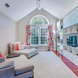 マイアミの大きいビーチスタイルのおしゃれなホームオフィス・書斎 (ライブラリー、ベージュの壁、濃色無垢フローリング、造り付け机、茶色い床) の写真