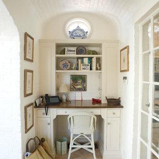Bild på ett litet maritimt hemmabibliotek, med vita väggar, klinkergolv i terrakotta, ett inbyggt skrivbord och beiget golv
