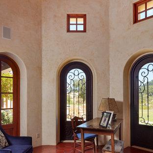 Immagine di uno studio mediterraneo con pareti beige, scrivania autoportante e pavimento rosso