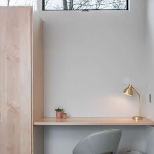 Example of a small danish built-in desk concrete floor and gray floor study room design in Other with white walls