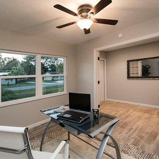 タンパの中くらいのコンテンポラリースタイルのおしゃれなホームオフィス・書斎 (グレーの壁、ラミネートの床、暖炉なし、自立型机、グレーの床) の写真