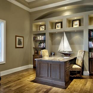 Idéer för ett stort medelhavsstil hemmabibliotek, med gröna väggar, mellanmörkt trägolv och ett inbyggt skrivbord