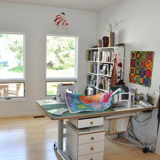 Imagen de despacho de estilo de casa de campo, pequeño, con paredes blancas, suelo de bambú y escritorio independiente