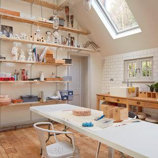 Создайте стильный интерьер: большая домашняя мастерская в скандинавском стиле с серыми стенами, паркетным полом среднего тона и отдельно стоящим рабочим столом без камина - последний тренд