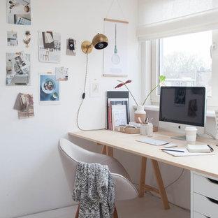 Пример оригинального дизайна: маленькая домашняя мастерская в скандинавском стиле с белыми стенами, деревянным полом и отдельно стоящим рабочим столом без камина