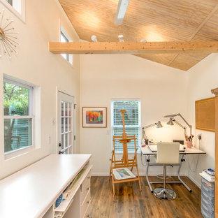 Skandinavisk inredning av ett litet hemmastudio, med vita väggar, laminatgolv, en öppen hörnspis, ett inbyggt skrivbord och brunt golv