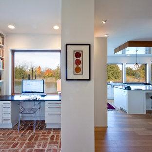 インディアナポリスの小さいコンテンポラリースタイルのおしゃれなホームオフィス・書斎 (白い壁、レンガの床、暖炉なし、造り付け机) の写真
