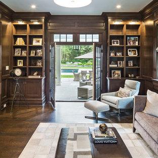 Exempel på ett stort klassiskt arbetsrum, med ett bibliotek, bruna väggar, mörkt trägolv och brunt golv