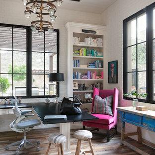 Inredning av ett lantligt mellanstort hemmabibliotek, med vita väggar, mellanmörkt trägolv och ett inbyggt skrivbord