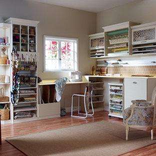 Mittelgroßes Mid-Century Nähzimmer ohne Kamin mit hellem Holzboden, Einbau-Schreibtisch, beigem Boden und beiger Wandfarbe in Detroit