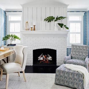 Cette photo montre un bureau bord de mer de taille moyenne avec un mur bleu, une cheminée standard, un manteau de cheminée en brique, un bureau indépendant, un sol marron, du papier peint et un sol en bois clair.