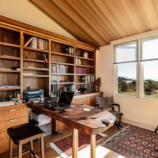 Cette photo montre un bureau rétro avec un mur beige, un sol en bois foncé et un bureau intégré.