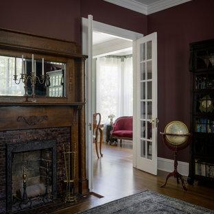 Modelo de despacho tradicional con suelo de madera en tonos medios, estufa de leña, marco de chimenea de ladrillo, escritorio independiente y suelo marrón
