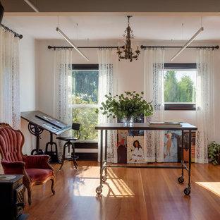 Idee per un atelier chic con pareti bianche, pavimento in legno massello medio, stufa a legna, cornice del camino in mattoni, scrivania autoportante e pavimento marrone