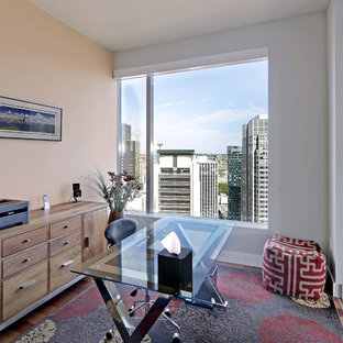 Small trendy freestanding desk medium tone wood floor home office photo in Seattle with orange walls