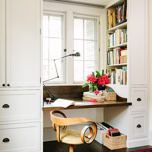 Example of an arts and crafts built-in desk dark wood floor home office design in Portland with white walls