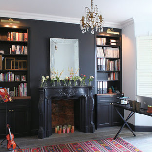 This is an example of a classic home office and library in London with black walls, dark hardwood flooring, a standard fireplace, a plastered fireplace surround, a freestanding desk and black floors.