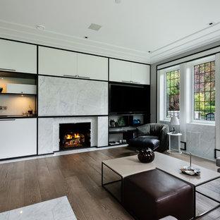 Foto de despacho de estilo zen, grande, con paredes grises, suelo de madera en tonos medios, chimenea tradicional, marco de chimenea de piedra, escritorio empotrado y suelo marrón