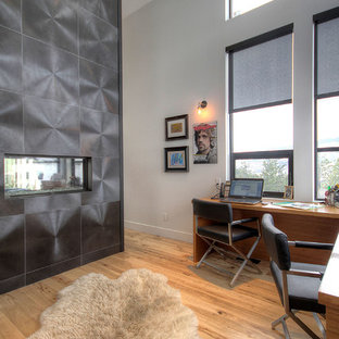 Photo of a large modern home office in Vancouver with white walls, medium hardwood flooring, a standard fireplace, a built-in desk and a metal fireplace surround.