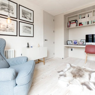 This is an example of a scandinavian study in London with beige walls, light hardwood flooring, a built-in desk and beige floors.