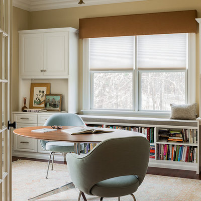 Transitional freestanding desk dark wood floor study room photo in Boston with beige walls and no fireplace