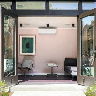 На фото: маленькая домашняя мастерская в стиле модернизм с розовыми стенами, полом из винила, встроенным рабочим столом и коричневым полом с