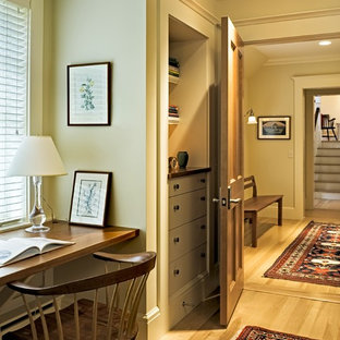 Ornate built-in desk medium tone wood floor home office photo in Burlington with beige walls