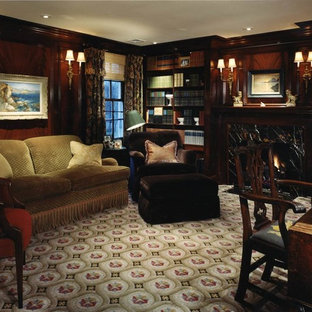 バーミングハムの中くらいのトラディショナルスタイルのおしゃれなホームオフィス・書斎 (標準型暖炉、ライブラリー、茶色い壁、カーペット敷き、木材の暖炉まわり、自立型机、マルチカラーの床) の写真