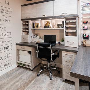 Klassisk inredning av ett mellanstort hemmabibliotek, med beige väggar, klinkergolv i porslin, ett inbyggt skrivbord och brunt golv