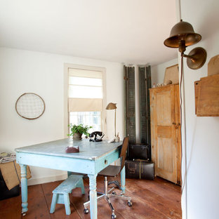 Cottage chic freestanding desk medium tone wood floor home office photo in Boston with white walls