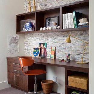 デンバーのエクレクティックスタイルのおしゃれなホームオフィス・仕事部屋 (ベージュの壁、カーペット敷き、造り付け机、黒い床) の写真