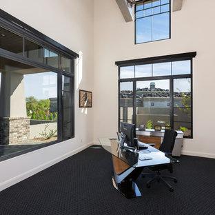 フェニックスの大きいコンテンポラリースタイルのおしゃれなホームオフィス・書斎 (白い壁、カーペット敷き、暖炉なし、自立型机、黒い床) の写真