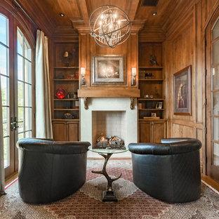 Exempel på ett mellanstort klassiskt hemmabibliotek, med en standard öppen spis, bruna väggar, mellanmörkt trägolv, en spiselkrans i betong, ett fristående skrivbord och brunt golv