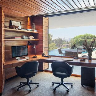 ミッドセンチュリースタイルのおしゃれな書斎 (茶色い壁、カーペット敷き、造り付け机、グレーの床、暖炉なし、板張り天井、板張り壁) の写真
