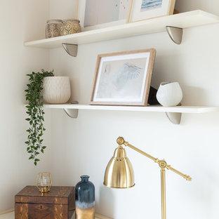 Aménagement d'un petit bureau scandinave avec un mur blanc, un sol en bois brun et un bureau intégré.