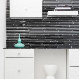 Idee per un ampio studio minimal con pareti nere, pavimento in gres porcellanato e scrivania incassata