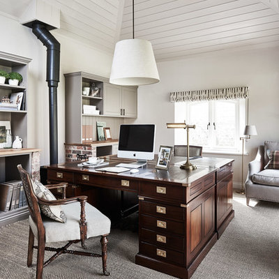 Study room - traditional freestanding desk carpeted study room idea in Wiltshire with white walls and a wood stove