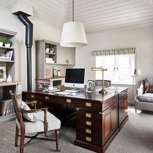 Bild på ett lantligt hemmabibliotek, med vita väggar, heltäckningsmatta, en öppen vedspis och ett fristående skrivbord