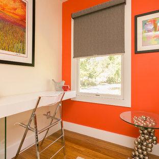 Idee per un atelier bohémian di medie dimensioni con pareti arancioni, pavimento in legno massello medio, nessun camino, scrivania autoportante e pavimento marrone