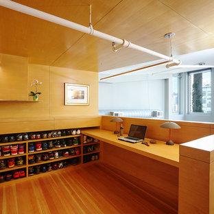 Modern inredning av ett hemmabibliotek, med mellanmörkt trägolv och ett inbyggt skrivbord