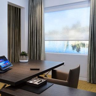 Idee per un piccolo ufficio design con pareti grigie, pavimento in bambù, scrivania autoportante e pavimento marrone