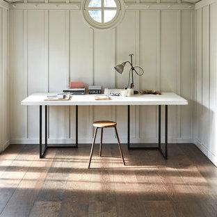 Inredning av ett klassiskt hemmabibliotek, med mellanmörkt trägolv, ett fristående skrivbord och grå väggar