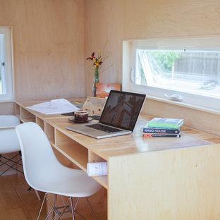 Bild på ett litet funkis hemmastudio, med ett inbyggt skrivbord och bambugolv