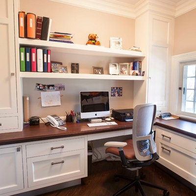 Example of a transitional built-in desk home office design in New York