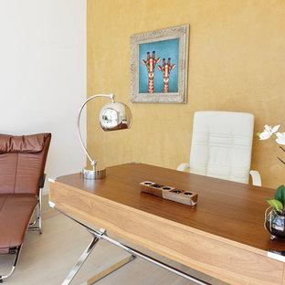 Immagine di un piccolo ufficio mediterraneo con pareti gialle, parquet chiaro, nessun camino e scrivania autoportante