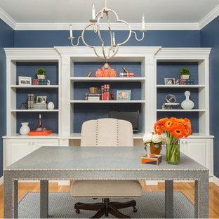 Idee per un ufficio chic di medie dimensioni con pareti blu, parquet chiaro e scrivania autoportante